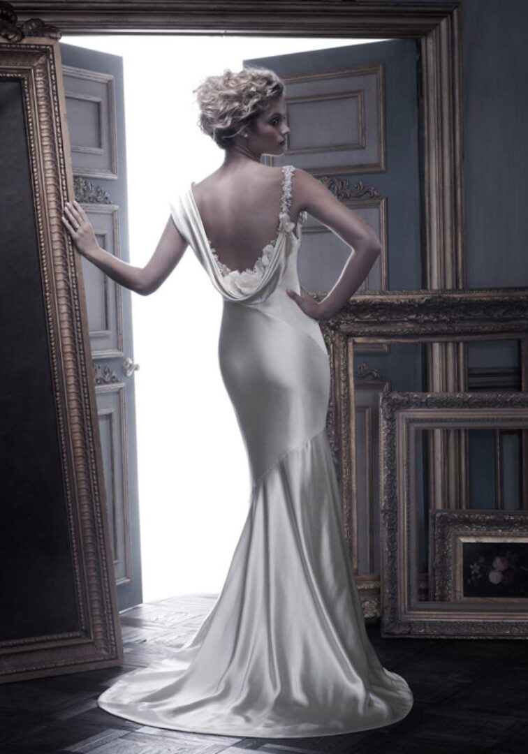 """This Silk Charmeuse gown has a dramatic draped neckline and deep """"V"""" back accented with a beaded shoulder strap with roses, fresh water, and blush pearls.  Fabric: Silk Charmeuse Available In: Champagne/Silver, Ivory/Silver Shown In: Champagne/Ivory/Silver"""